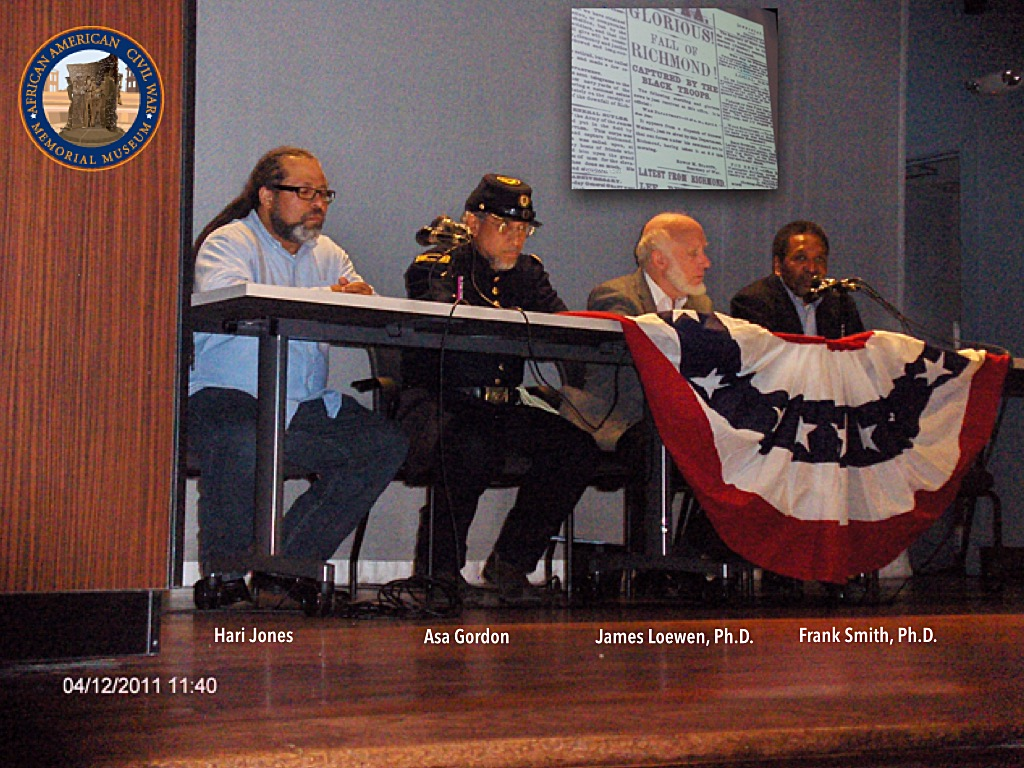 Hari Jones, Asa Gordon, James Loewen,, Ph.D., and. Frank. Smith, Ph.D. are seated on stage at a table